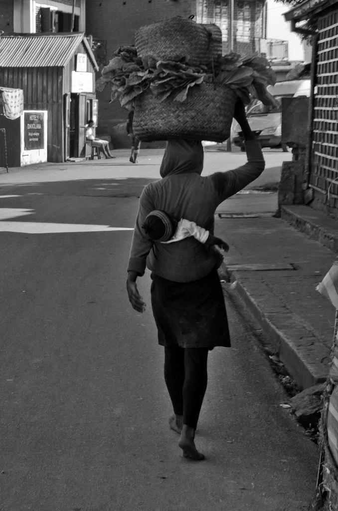 Mujer malgache llevando sus mercancías sobre su cabeza y su bebé a la espalda
