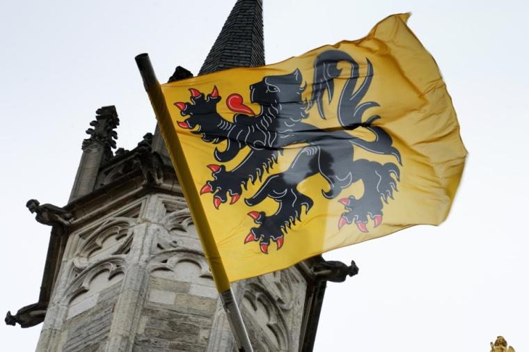 La bandera flamenca hondeando frente al edificio del Ayuntamiento de Brujas